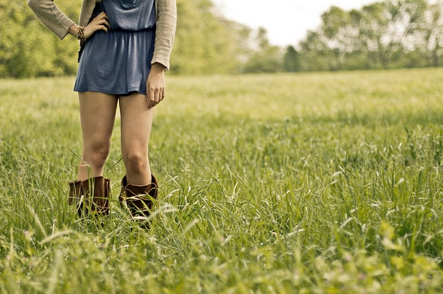 dívka stojí na louce